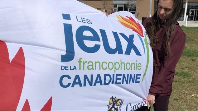 Une organisatrice des jeux tient le drapeau gonflé par le vent.