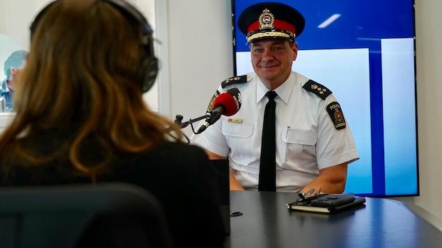 Un homme en uniforme de police parle dans un micro