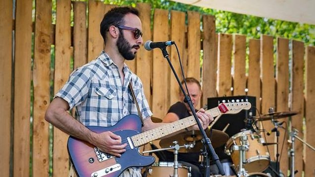 En avant-plan, un homme portant une chemise à carreaux qui joue à guitare devant un micro ; à sa gauche, un bassiste vêtu de noir.