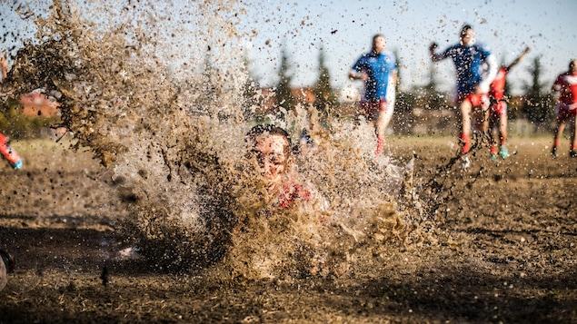 Un joueur de rugby s'éclabousse en tombant dans la boue, tandis qu'on voit d'autres joueurs à l'arrière.