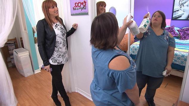 Carolane, atteinte de trisomie 21, nettoie son miroir sous l'oeil attentif d'Isabelle, son éducatrice