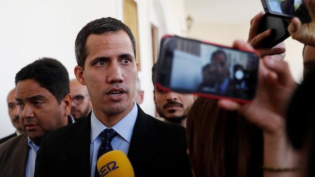 Juan Guaido parle dans un micro jaune d'une journaliste, il est en costume sombre et porte une cravate à pois.