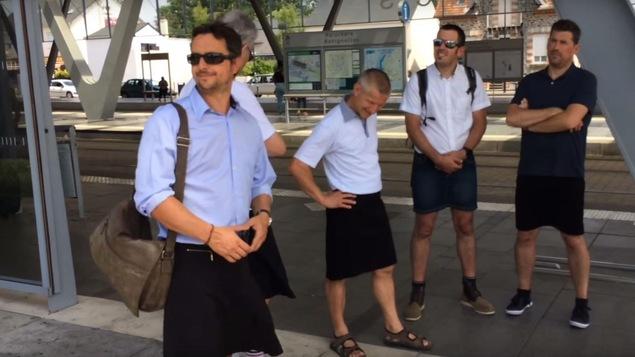 Cinq chauffeurs d'autobus en jupe discutant sur un quai