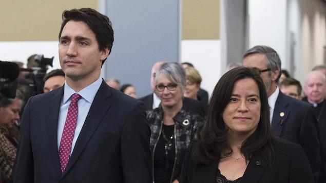 Justin Trudeau et Jody Wilson-Raybould se tiennent côte à côte, mais regardent dans des directions opposées.