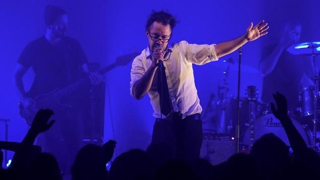 Keith Kouna se tient debout sur scène, micro à la main, sur fond d'éclairage bleu électrique.