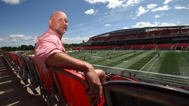 M. Evraire est assis dans le stade des Rouges et Noirs d'Ottawa.