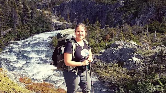 Une femme en randonnée pose pour la caméra sur un mont, près d'un cours d'eau.