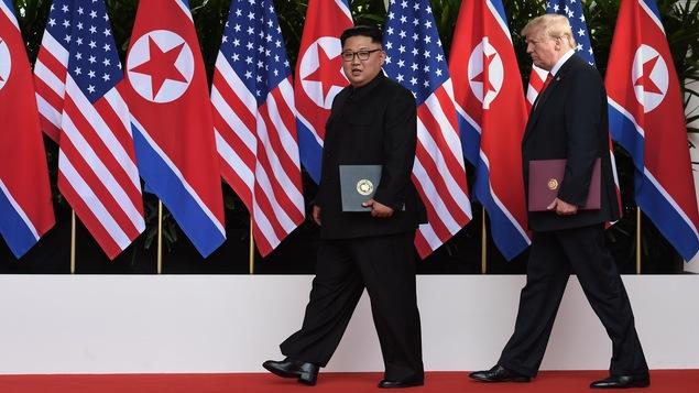 Kim Jong-un et Donald Trump tiennent des documents de l'entente sur la dénucléarisation de la Corée du Nord et marchent devant des drapeaux de leur pays respectif.