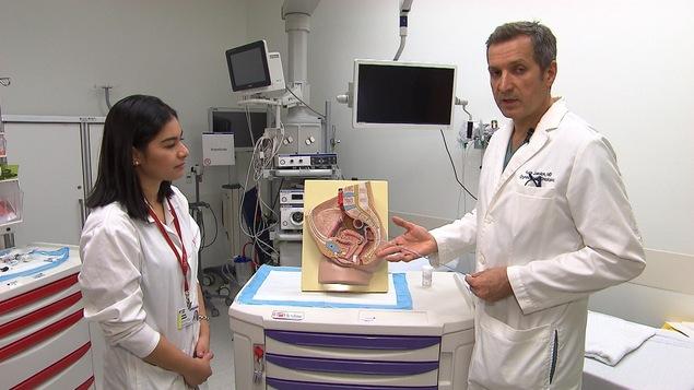 Le Dr Kardon pointe un schéma reproduisant l'intérieur de l'appareil reproducteur féminin.