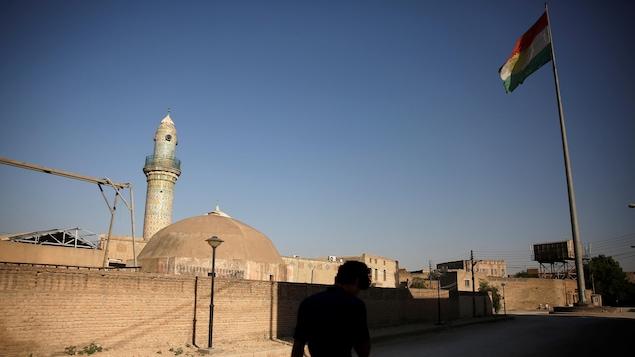 Un homme marche près de la citadelle où flotte un drapeau kurde.