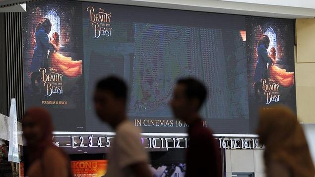 Des cinéphiles font la file dans un cinéma qui contient une affiche de « La Belle et la Bête », à Kuala Lumpur en Malaisie