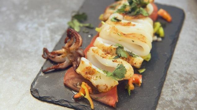 Un plat de calmar grillé cuit à la  plancha sur une planche de service.