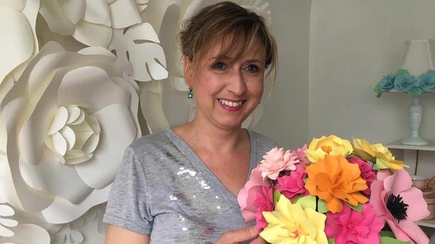 Chantal Larocque tenant un bouquet de fleurs en papier