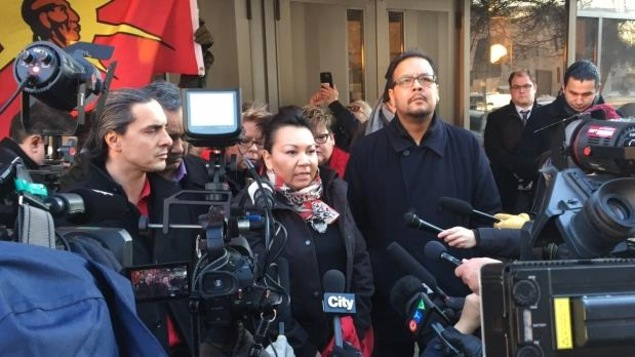 Des leaders autochtones sont entourés de micros et de caméras devant le palais de justice de Winnipeg.