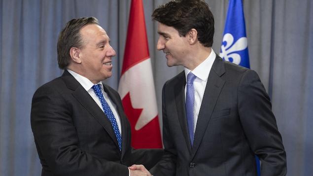 François Legault et Justin se serrent la main.