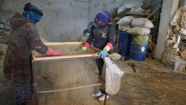 Des femmes tamisent de la poudre dans une pièce fermée.