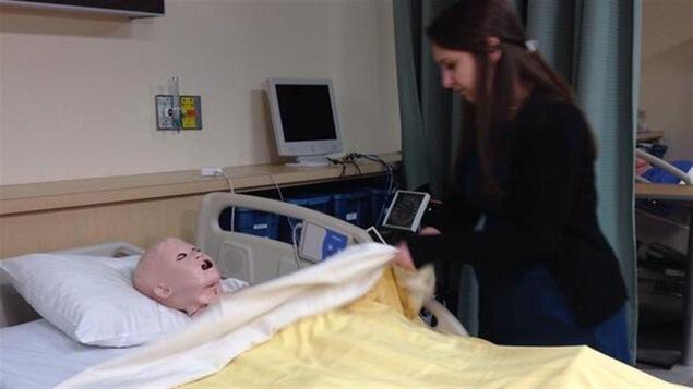 Une étudiante en sciences infirmières pratique sur un mannequin.