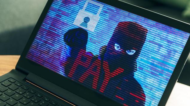 Un écran d'ordinateur montre un pirate informatique qui exige un paiement.