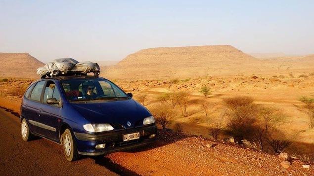 Une voiture bleue sur le bord de la route dans un lieu désertique