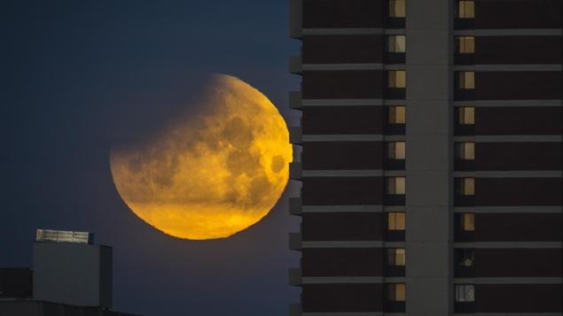 Une vue de la lune avec un bâtiment en avant plan.