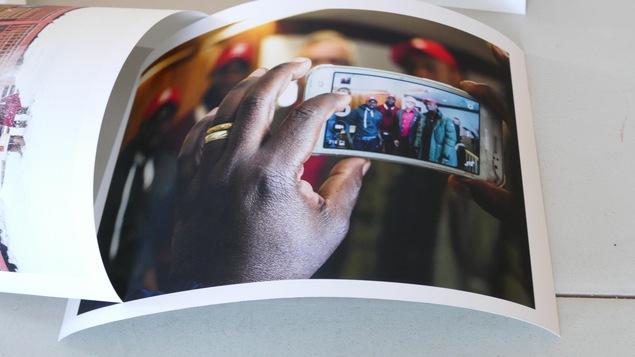 Une main tient un cellulaire qui montre une photo de groupe de 3 hommes noirs et 1 homme blanc.