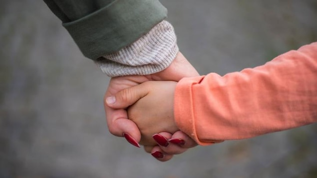 Une adulte et un enfant qui se tiennent la main