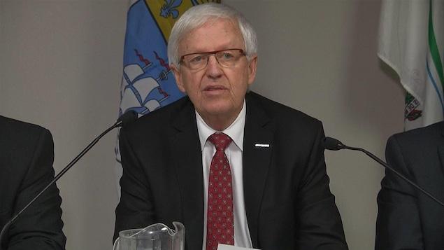 Le maire de Brossard, Paul Leduc, lors d'une conférence de presse en décembre 2014, avec le drapeau de la ville en arrière-plan.