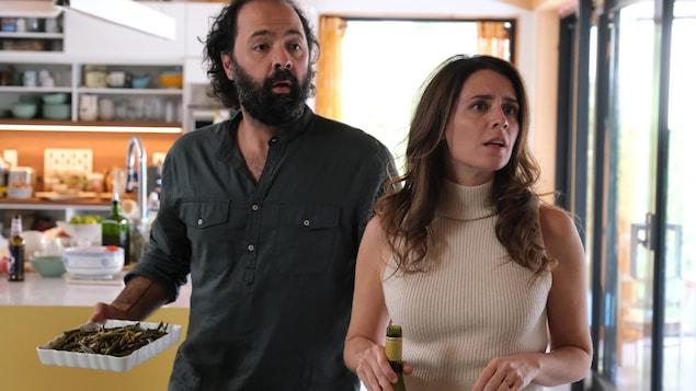 Deux personnes se tiennent debout dans une cuisine. Mani Soleymanlou tient un plat de service sur lequel se trouvent des aliments. Mélissa Désormeaux-Poulin tient une bouteille de vin.