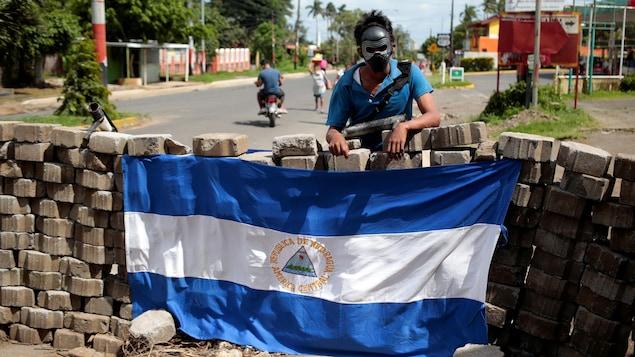 Un manifestant masqué pose devant un drapeau du Nicaragua.