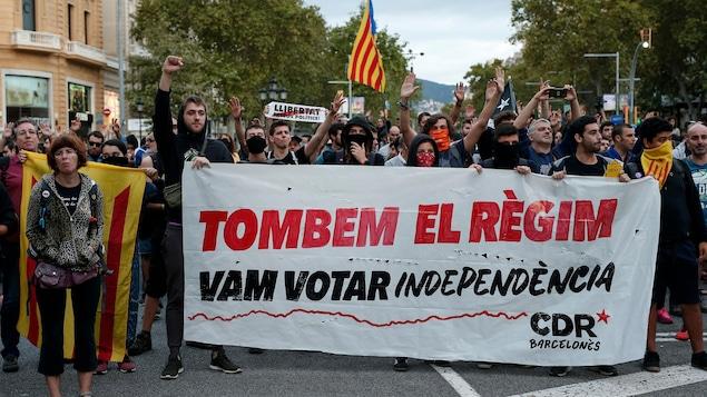 Des manifestants catalans en faveur de l'indépendance manifestent dans les rues de Barcelone, tenant une banderole sur laquelle on peut lire : « Faisons tomber le régime ».