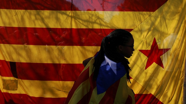 Une femme portant un drapeau indépendantiste catalan passe devant un autre drapeau coloré durant une manifestation à Barcelone.