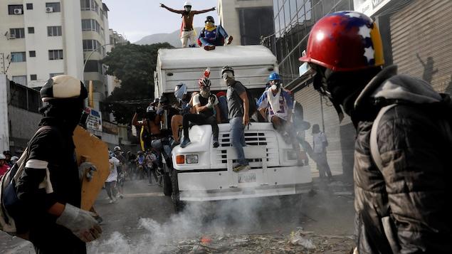Des manifestants portant des masques à gaz et des casques sont montés sur un camion. Ils sont entourés d'une fumée blanche, qui est en fait du gaz.