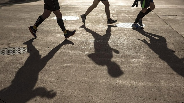 Trois ombres de coureurs sur l'asphalte