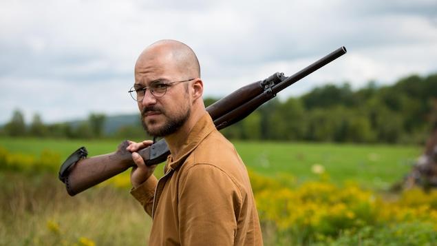 Marc-André Grondin, un fusil sur l'épaule, dans une scène du film « Les affamés »