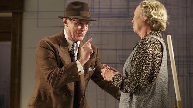 Chapeau sur la tête, lunettes rondes sur le nez et portant veston et cravate, le comédien discute avec Louise Turcot.