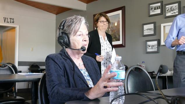 Une femme installée à un micro d'un studio de radio mobile.
