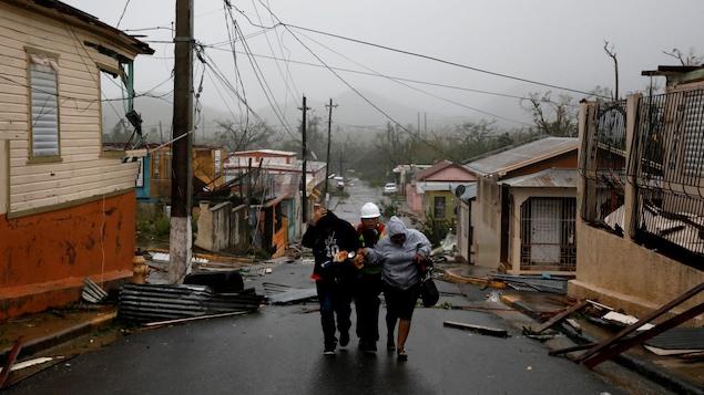 Un secouriste aide deux personnes après le passage de l'ouragan Maria à Guayama, Porto Rico.