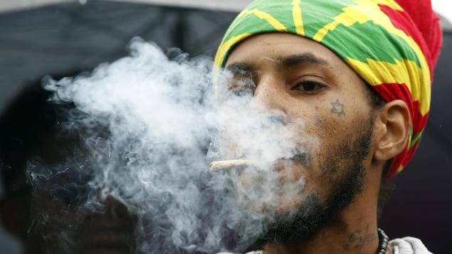 Un jeune homme fume un joint.