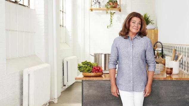 L'animatrice est debout devant un comptoir dans une cuisine blanche et elle sourit.