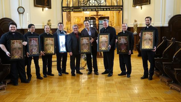 Mario Pelchat, les huit prêtes et le maire de Québec, Régis Labeaume soulignent le disque or de l'album Agnus Dei.