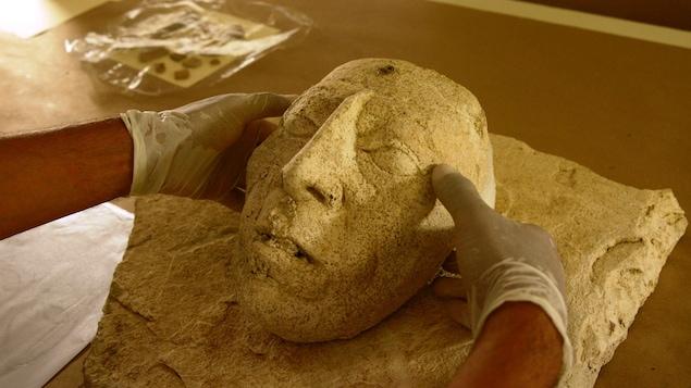 Des mains tiennent le masque du souverain maya Pacal le Grand.