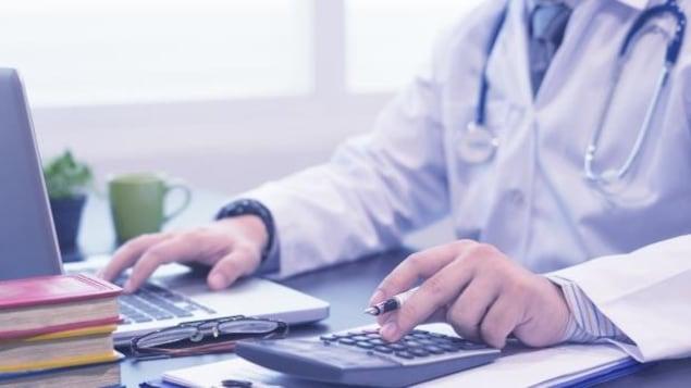 Un médecin anonyme assis devant son ordinateur