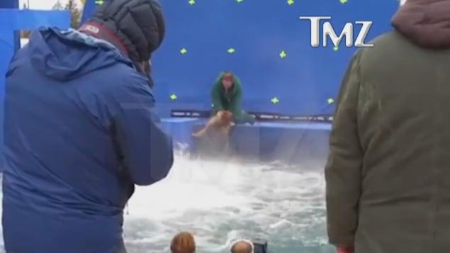 Image tirée d'un vidéo publiée par TMZ : un homme jette un chien effrayé dans des eaux turbulententes.
