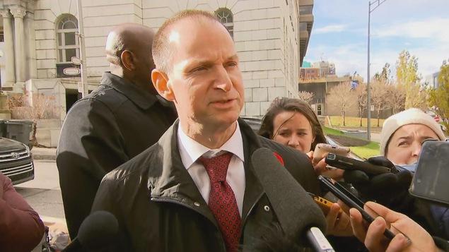 Le ministre des Finances  Éric Girard, entre le parlement de Québec et les micros des journalistes.