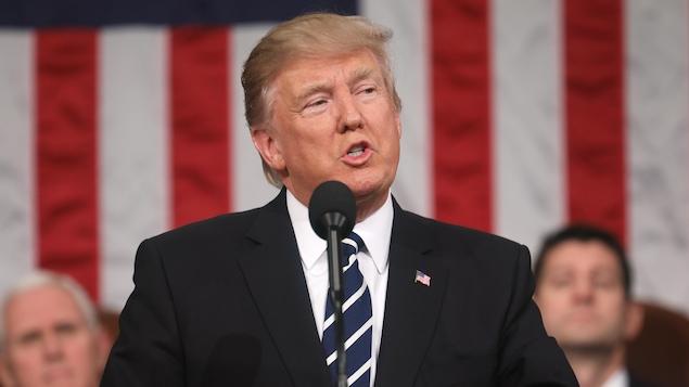 Le président américain Donald Trump derrière un micro et devant la drapeau américain, prononce son premier discours devant les deux chambres du Congrès.