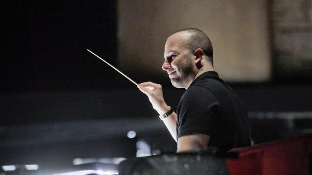 Le chef d'orchestre Yannick Nézet-Séguin tenant une baguette de direction dans une salle de répétition