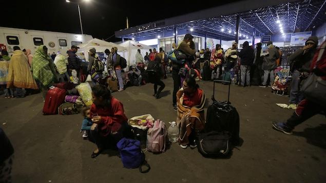 Des adultes s'enveloppant de couvertures et quelques enfants attendent avec leurs bagages à l'extérieur en soirée le feu vert des autorités pour entrer en Équateur