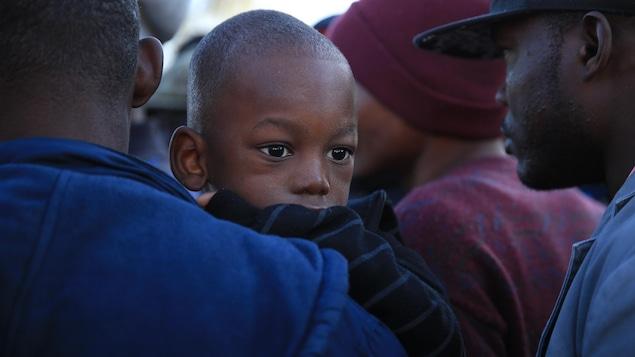 Photo d'un enfant haïtien dans les bras de son père