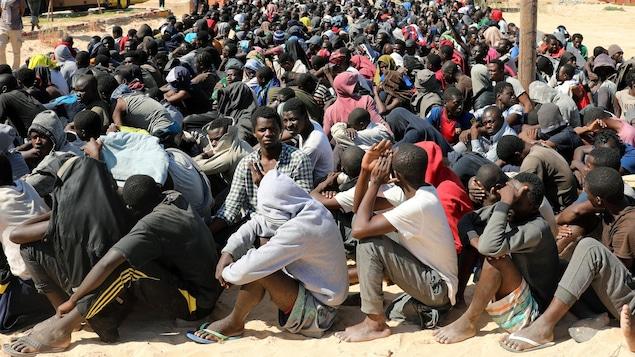 Des centaines d'hommes sont assis parterre dans le sable en rang serré.