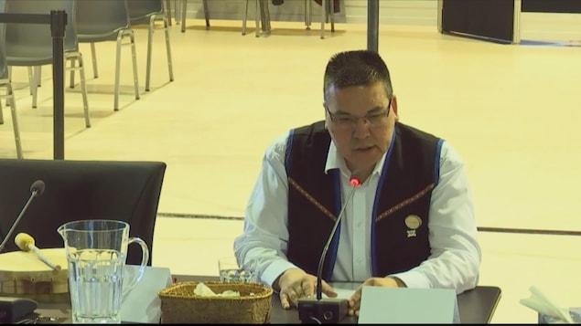 Le chef de Uashat-Maliotenam, Mike McKenzie, attablé devant un micro